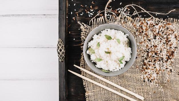 Grains and chopsticks near boiled rice