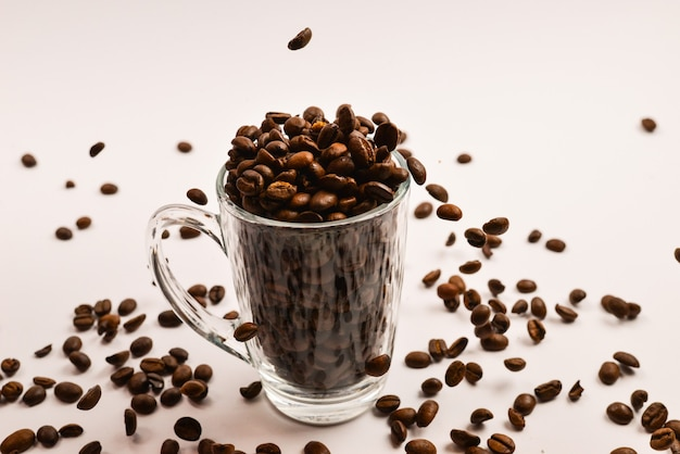 Grains of coffee are poured into a glass cup on a white background