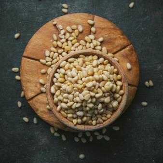 Зерна в деревянном шаре на деревянном куске и темной таблице. вид сверху.