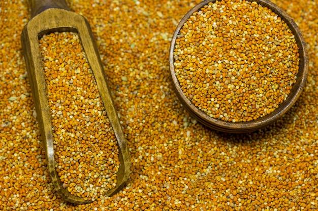 Grains of millet in a wooden scoop