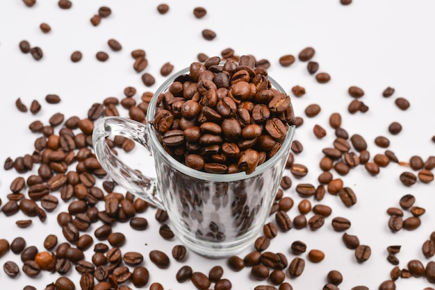 コーヒーの粒が白い背景の上のガラスのコップに注がれる
