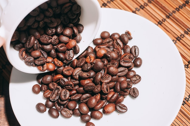 Зерна кофе в чашке и на тарелке на деревянном столе