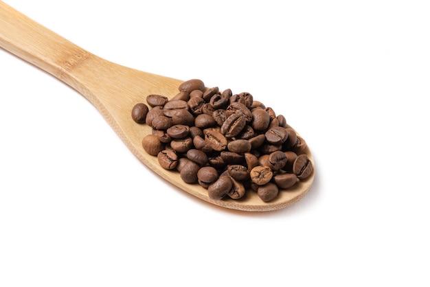 Зерна кофе на деревянной ложке на белом фоне