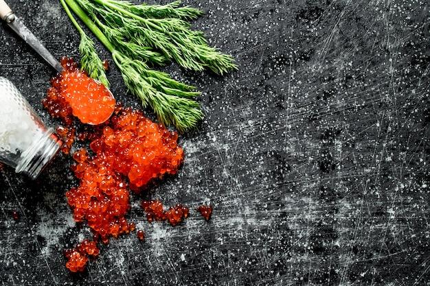 Зерна красной икры с солью и укропом. на черном деревенском фоне
