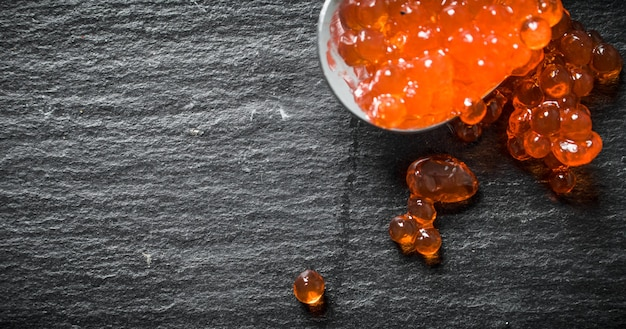 Grains of red caviar on a spoon. on black rustic