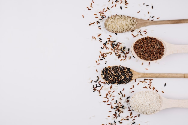 Grains spilled around spoons with rice