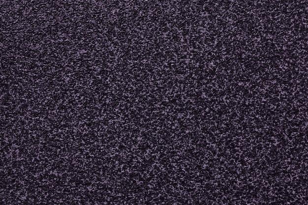 斑点模様の粒子の粗い黒と紫の背景。
