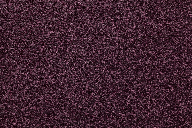 Grainy dark purple background with spotted pattern.