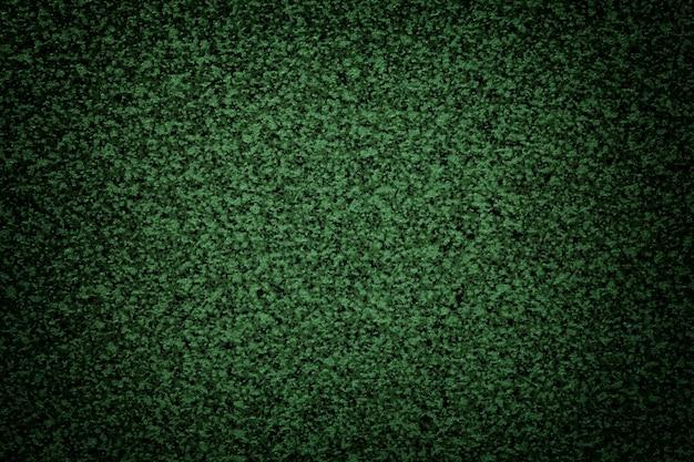 暗いビネットとテーブルトップの粒子の粗い緑の背景。小さなパン粉パターンで抽象的な表面をテクスチャリングします。