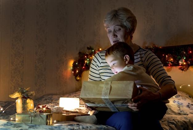 花輪の光のある部屋でクリスマスプレゼントを開くソファに座っているgramdmotherと孫