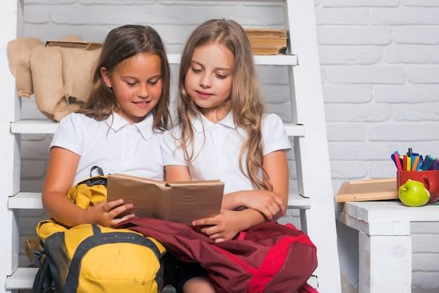 小さな子供たちの手にある文法書。