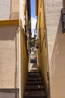グラナダ、アンダルシア、スペイン-2019年5月26日:古い家々の間に階段がある狭い通り、グラナダの建築。