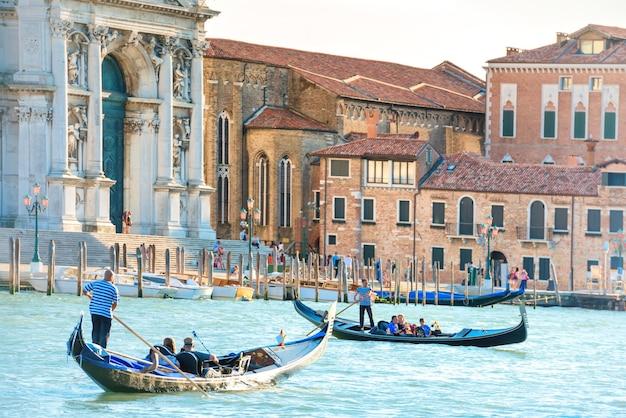 화창한 날에는 곤돌라, 관광객, 산타 마리아 델라 살루트 대성당이 있는 대운하. 베니스, 이탈리아