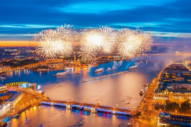 Грандиозный фейерверк над водами невы в санкт-петербурге, виден дворцовый мост, петропавловская крепость.