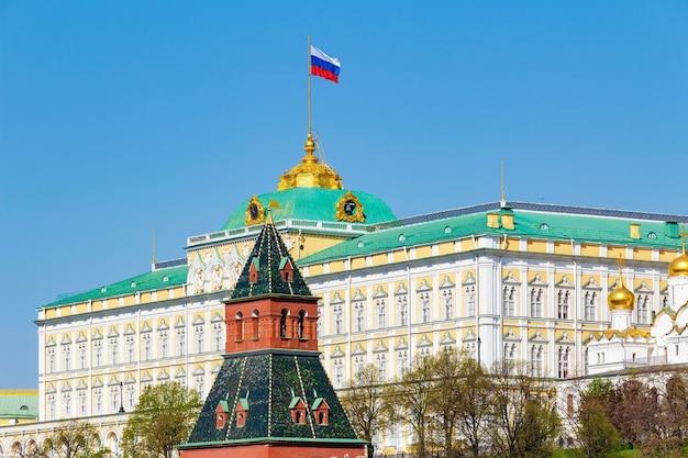 Большой кремлевский дворец с развевающимся флагом российской федерации на крыше против башни московского кремля на фоне голубого неба