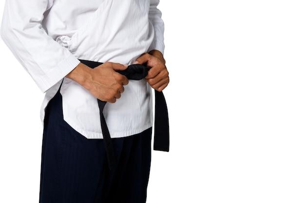 Великий мастер черный пояс тхэквондо учитель удерживает и завязывает пояс позы, студия части талии на белом фоне изолированы
