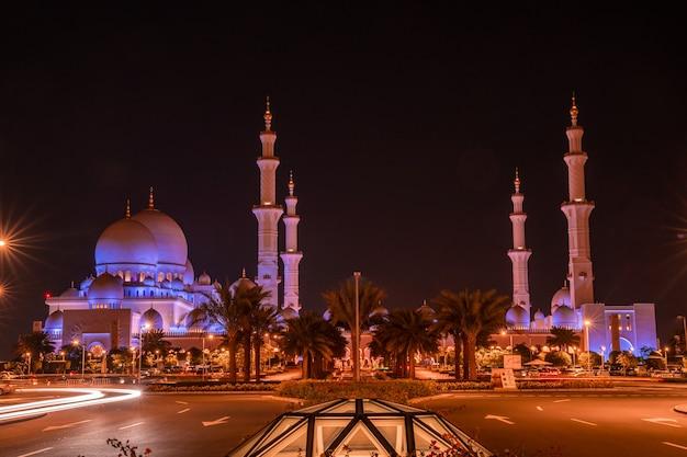 Большая мечеть в абу-даби ночью. панорамный вид снаружи мечети шейха зайда в оаэ с эпическим освещением.