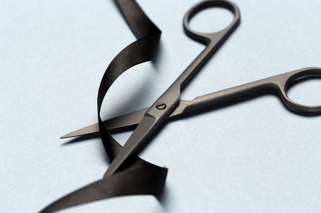 Grand opening illustrated with  scissors and a black ribbon