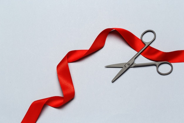 Grand opening illustrated with  scissors and a red ribbon