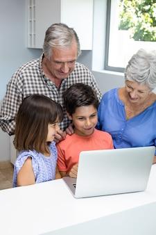 Grand parents and grandchildren interacting using laptop