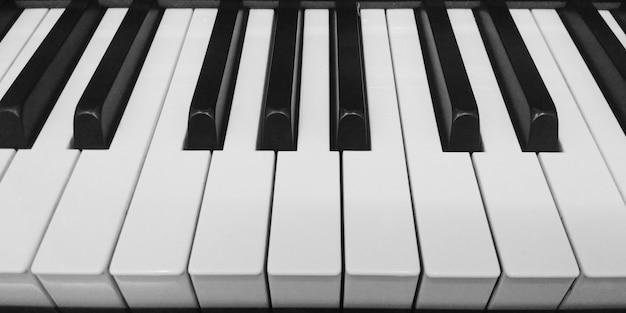 グランドピアノのキーボードの背景をクローズアップ