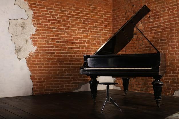 レンガの壁の近くに隆起した蓋とスツールを備えたグランドピアノ