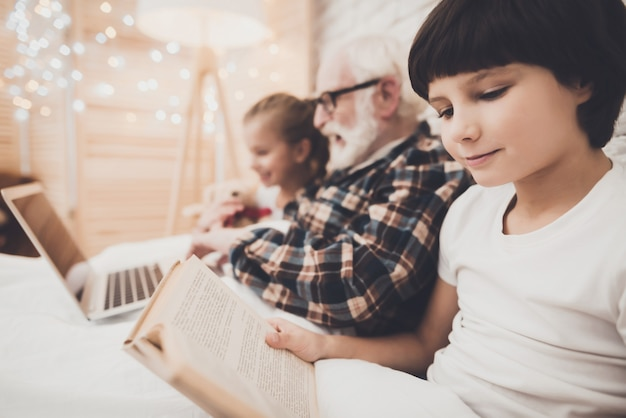 Grandad and children read and watch movies in bed.