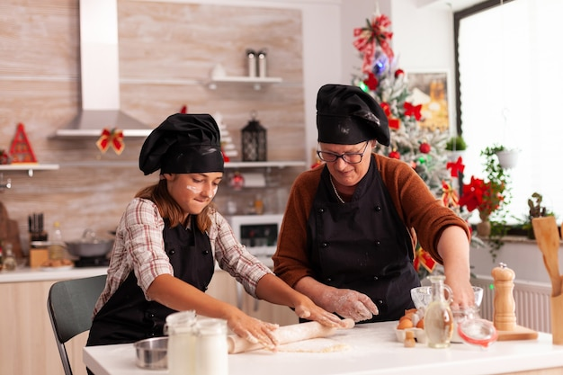 Grandchild cooking gingerbread dessert with grandmother