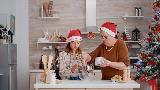 孫が自家製の伝統的なクッキー生地を準備する年配の女性を助けます