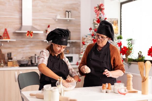 Grandchild preparing homemade dough with grandmother celebrating christmas season