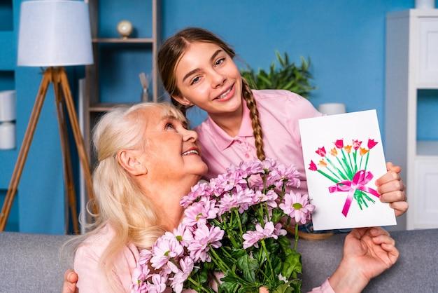 孫が家でおばあちゃんに花を贈る、幸せな家庭生活の瞬間