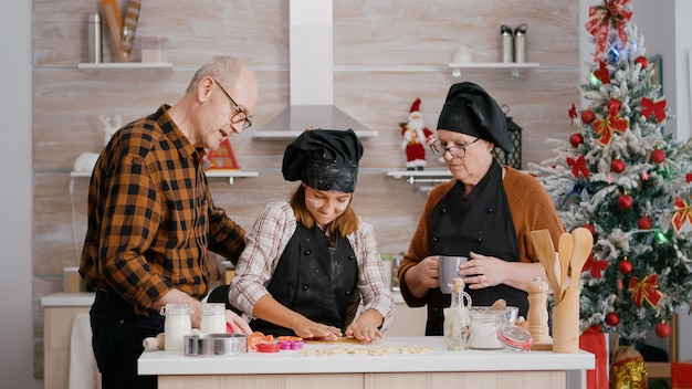 쿠키 모양을 사용하는 방법을 조부모에게 보여주는 손자