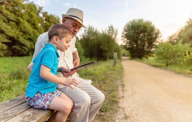 孫が祖父に公園のベンチで電子タブレットを使用するように教えています。世代の価値観の概念。