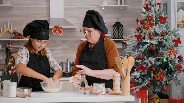 料理のキッチンで自家製の冬のビスケット生地を準備するエプロンを身に着けている孫
