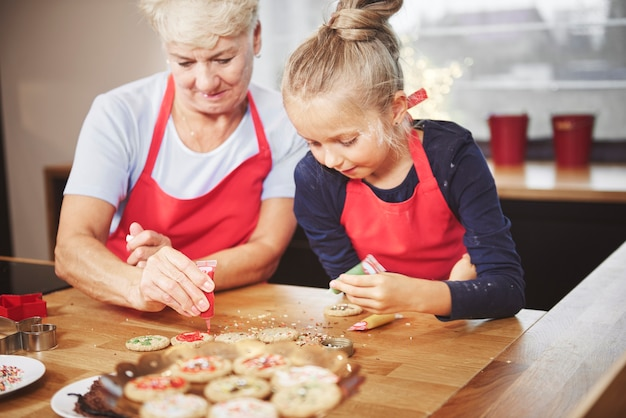 Grandchild with grandma decorating cookies with icing