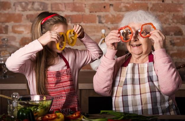 Внук с бабушкой держит ломтики перца