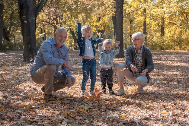孫と祖父母が公園に葉っぱを投げて一緒に時間を過ごす
