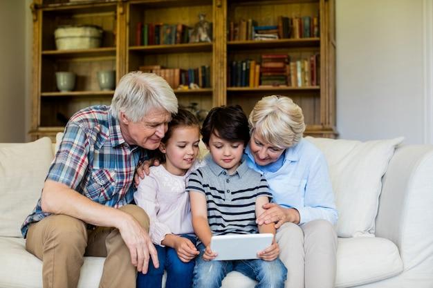 祖父母とデジタルタブレットを使用している孫