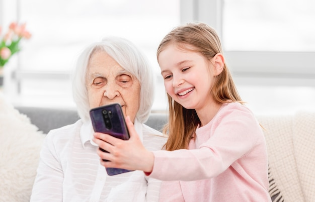 Granddaughetr making selfie on smartphone with her grandmother at home