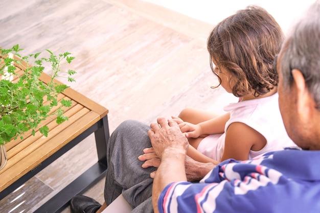 Внучка и дедушка трогательно руки сидят в профиль сзади с размытым фоном и низким коричневым деревянным столом
