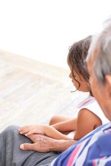 Внучка и дедушка трогательно руки, сидя в профиле с несфокусированным фоном