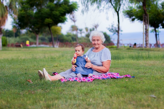 秋の公園を歩く孫と祖母