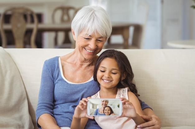 孫娘と祖母がリビングルームで携帯電話でselfieを取る