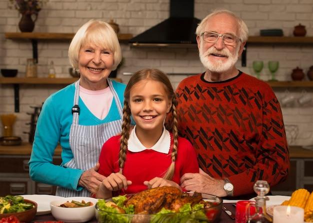 Внучка, бабушка и дедушка и глядя на камеру