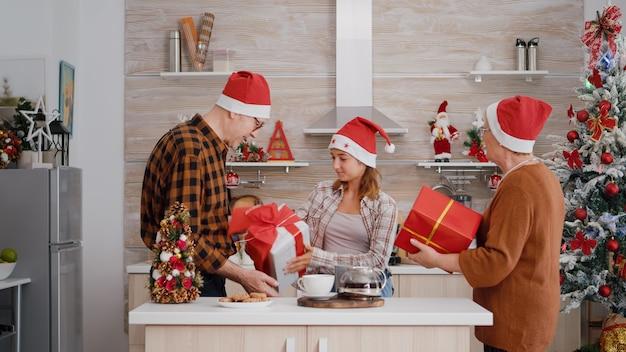 クリスマスを祝う祖父母にラッパーギフトプレゼントサプライズをもたらす孫娘