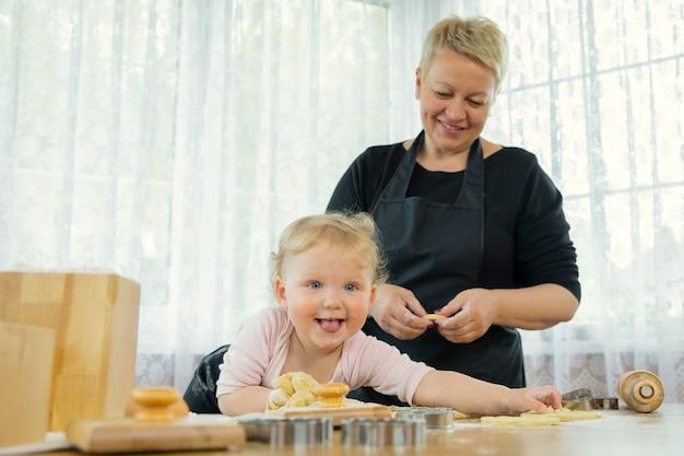 幸せな祖母がクッキーを作るのを手伝っている間、孫娘は小麦粉で汚れました