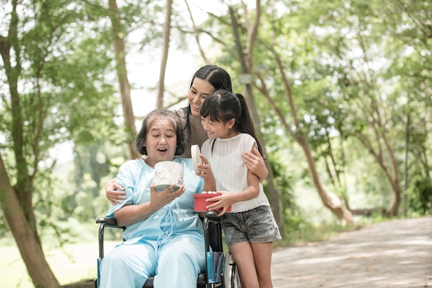 Granddaughter have surprise to grandmother sitting on wheelchair.