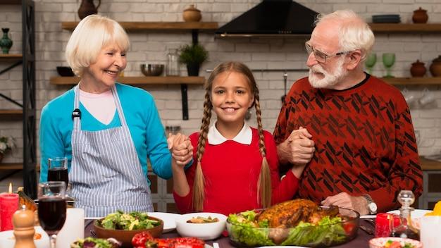 Внучка держит бабушку и дедушку и смотрит в камеру