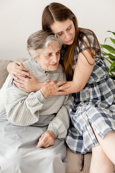 Granddaughter hugging grandma at home