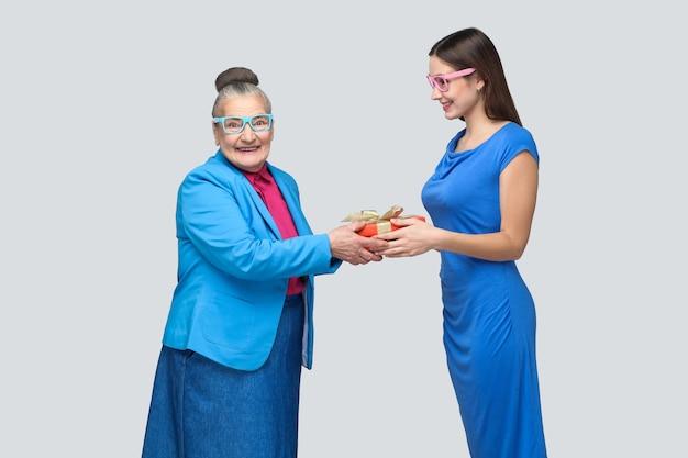 Внучка в голубом платье улыбается и делает подарок своей прекрасной бабушке, глядя в камеру с удивленным лицом. дружба, взаимопонимание. крытый, студийный снимок, изолированный на сером фоне.